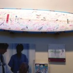 "ACCP's custom surfboard, a memento of their successful meeting in Hawai`i, mounted on handmade ""hands"" that they had carved for this special display.  Photo courtesy of ACCP."
